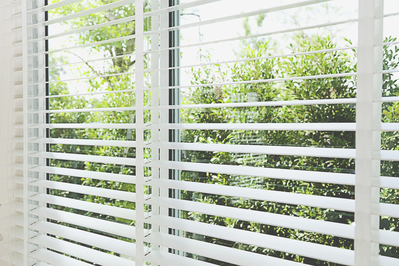 Venetian blinds with sun and greenery in background