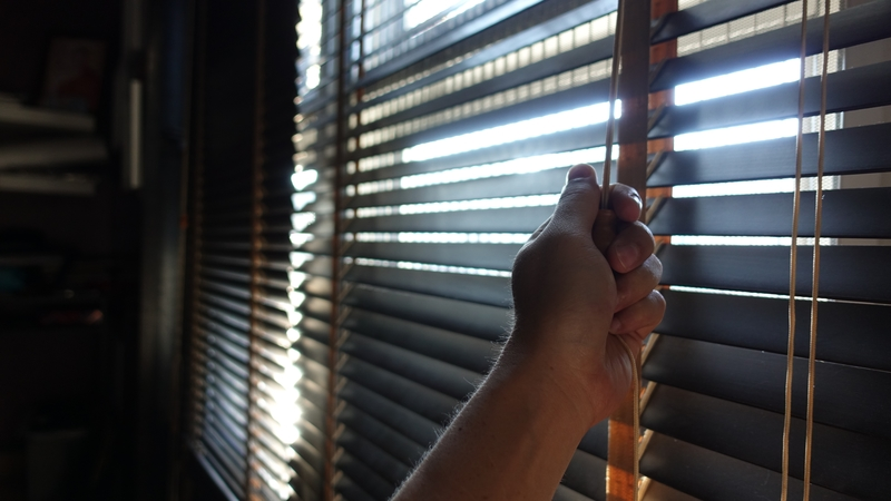 hand pulling up Venetian blinds