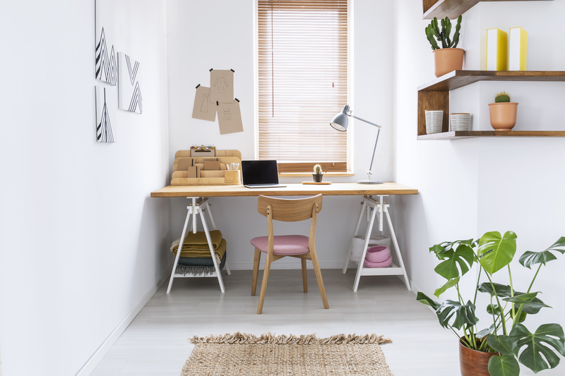 Desk by window with wooden blinds